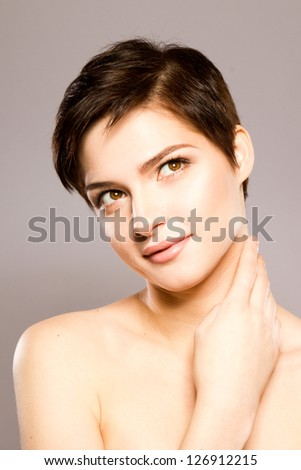 beautiful girl smiling with her hand on her neck