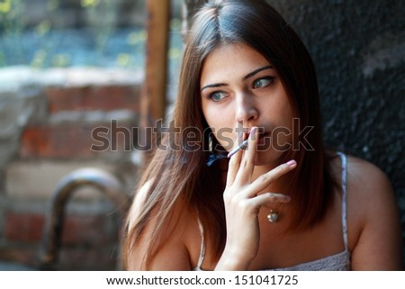 beautiful girl smokes and sad outdoor thinking about problems - stock photo