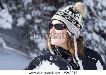Beautiful girl snowborder in winter forest in mountain