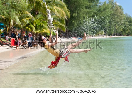 Beautiful girl splashing water while playing swing at the sea - stock photo