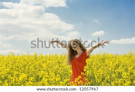 beautiful girl spreading her arms in the middle of a rapeseed(canola) field with blue cloudy sky, 'outdoor freedom' - stock photo