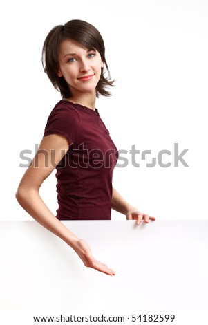 beautiful girl standing behind an empty white board and showing something - stock photo