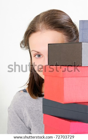 Beautiful  girl  standing  behind  boxes  and  watches. Focus on eye. - stock photo