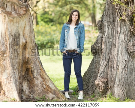 Beautiful girl standing between the trees and smiling. - stock photo