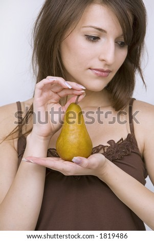 beautiful girl standing holding pear