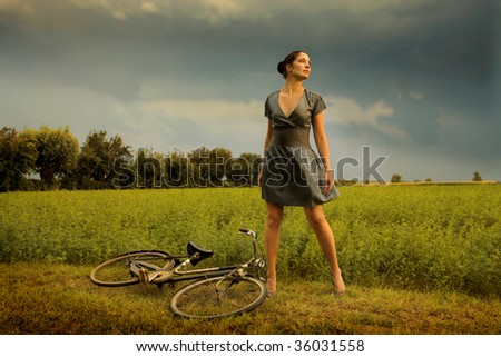 beautiful girl standing in a grass field next to old bicycle - stock photo