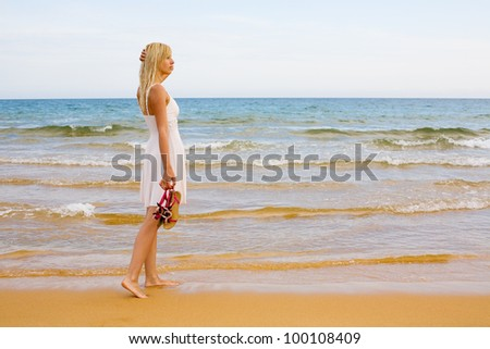 Beautiful girl standing in the evening by the sea - stock photo