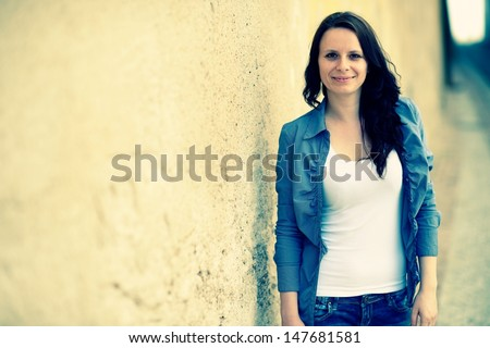 Beautiful girl standing near the wall