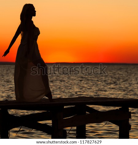 beautiful girl standing on a bridge at sunset ,silhuette - stock photo