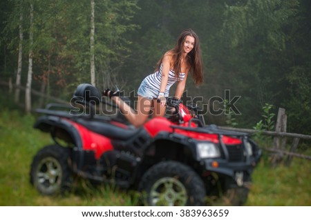 Beautiful girl standing on four-wheeler ATV. Smiling and looking towards the camera. Tilt shift lens blur effect
