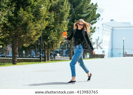 Beautiful girl standing on the street with coffee and glasses.
