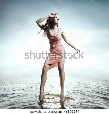 Beautiful girl standing on water - stock photo