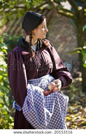 Beautiful girl standing outdoors in the orchard picking apples from the tree - stock photo