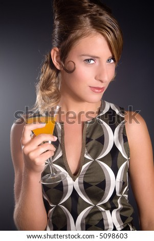 Beautiful girl standing with cocktail in hand with retro dress - stock photo