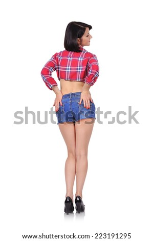 beautiful girl standing with her back with legs crossed - stock photo
