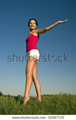 Beautiful girl stretches the outdoors. - stock photo