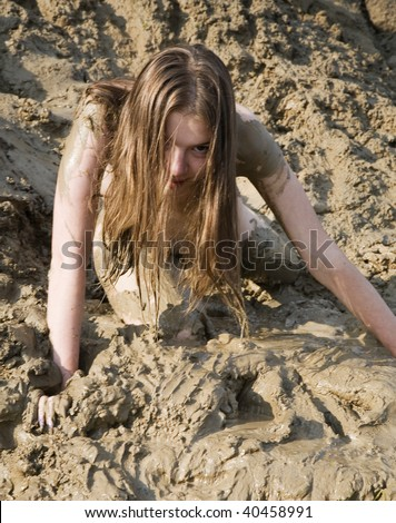 Beautiful girl struggling in the mud. very dirty - stock photo