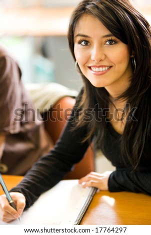 Beautiful girl studying in a classroom - smiling and writting on her notebook - stock photo