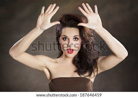 Beautiful girl surrenders and holding up her hands - stock photo