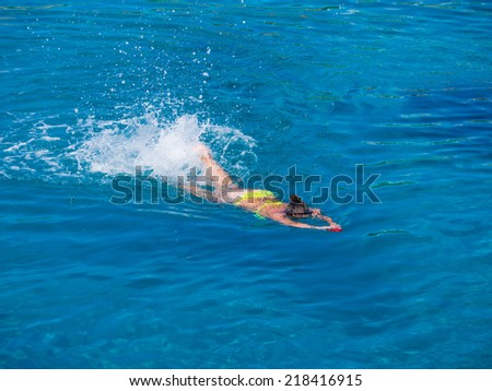 Beautiful girl swimming in blue water in the Ionian sea