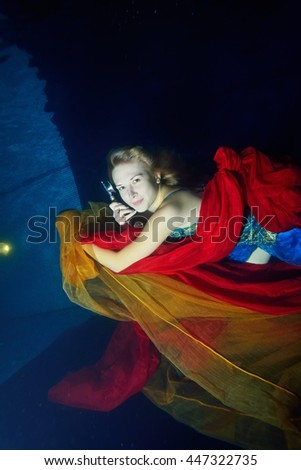 Beautiful girl swims underwater in a blue dress with red and orange cloth and talking on the phone on a blue background. Top view. Vertical orientation. - stock photo