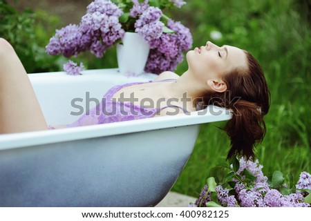 Beautiful girl takes a bath in the garden with lilac flowers, organic skin care - stock photo