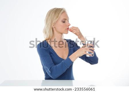 beautiful girl takes pill because she has sore head - stock photo