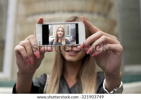 Beautiful girl taking selfie outside
