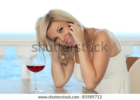 Beautiful girl talking on the phone in a cafe and drink wine - stock photo