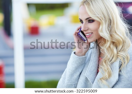 Beautiful girl talking on the phone on the street - stock photo
