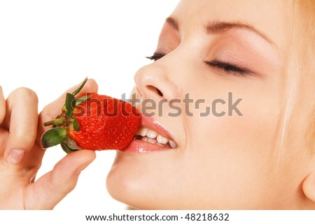 Beautiful girl tasting a strawberry, face portrait - stock photo