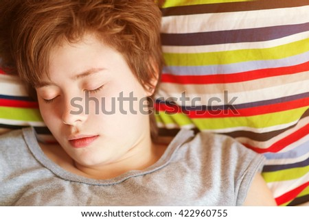 Beautiful girl teenager in the gray pajamas asleep in bed on colored striped pillow - stock photo