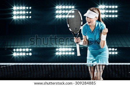 Beautiful girl tennis player with a racket on dark background wiht lights celebrating flawless victory - stock photo