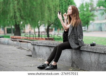 beautiful girl the photographer to apply makeup on a city street - stock photo
