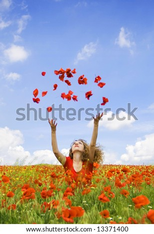 beautiful girl throwing poppies in the air, summer scenery - stock photo