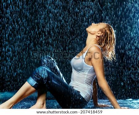 beautiful girl under raining water, black background - stock photo