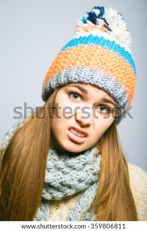 beautiful girl unhappy, knit cap, winter concept, photo studio, portrait of a woman isolated on gray background