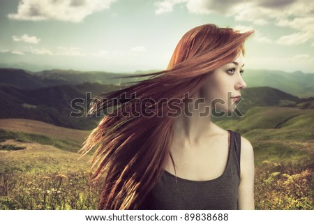 beautiful girl upland with hair blown by wind - stock photo