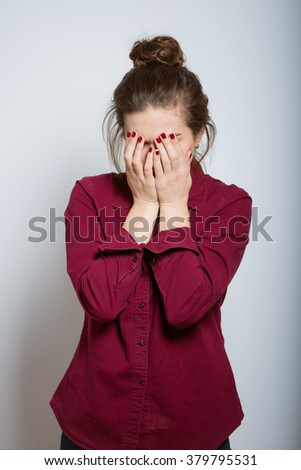 Beautiful girl upset covered her face, isolated on a gray background - stock photo