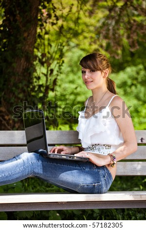 Beautiful girl using laptop outside during a summer day in the park. - stock photo
