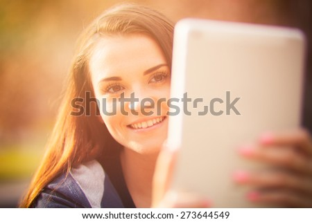 Beautiful girl using tablet or ebook outdoor