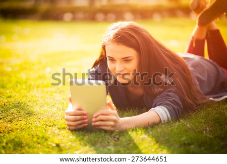 Beautiful girl using tablet or ebook outdoor laying on field - stock photo