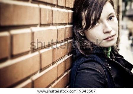 Beautiful girl waiting against brick wall - stock photo