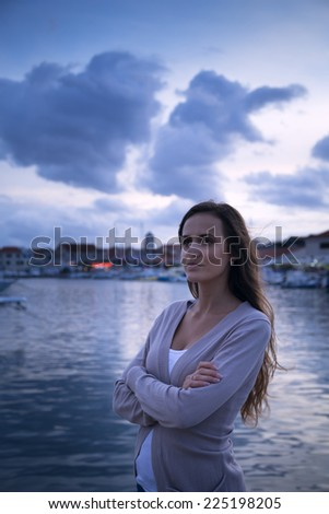 beautiful girl waiting in the evening marina in Croatia - stock photo