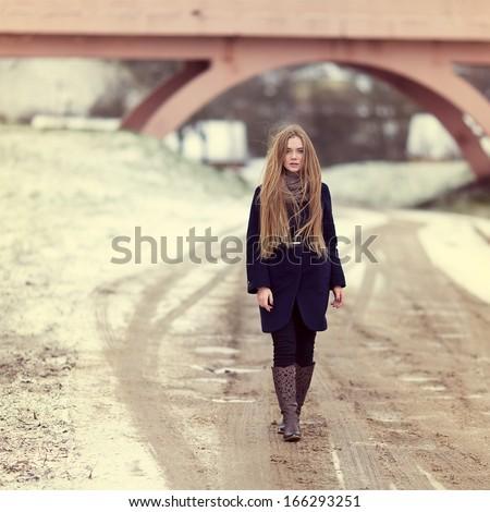Beautiful girl walking along a winter road near the bridge. Portrait in full growth - stock photo