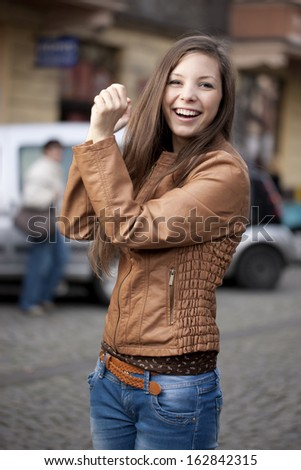 Beautiful girl walking and dancing on the street. - stock photo