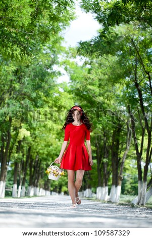Beautiful girl walking and holding basket full of flowers