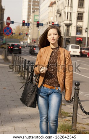 Beautiful girl walking and posing on the street. - stock photo