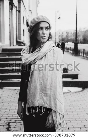 beautiful girl walking around the city in a beret and scarf