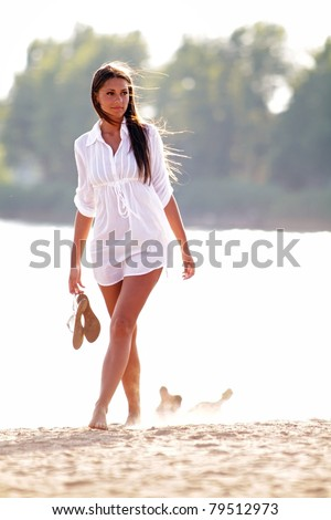 Beautiful girl walking down the beach at sunset - stock photo